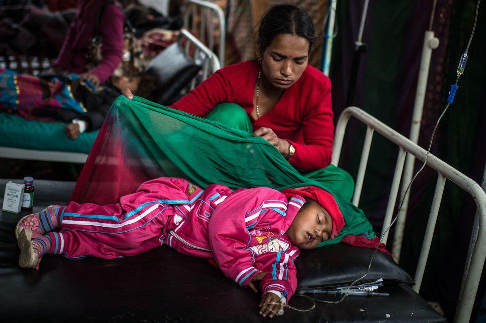 Sanjhana Tamang takes care of her 3-year-old daughter, Simran Tamang on April 13, 2015, as she lies in bed at a temporary hos