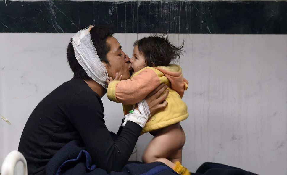 Nepalese resident Suresh Parihar plays with his 8-month-old daughter, Sandhaya, as he is treated for injuries in Kathmandu.