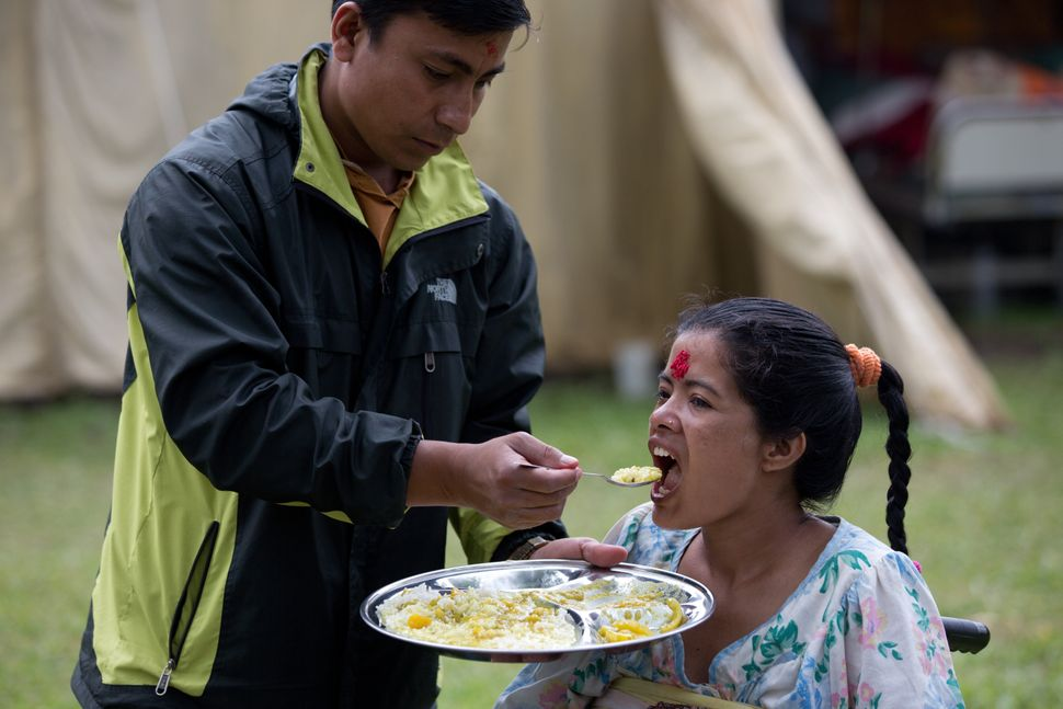 A Nepalese woman is fed by family member at the Nepali Military hospital in Kathmandu on April 29, 2015.