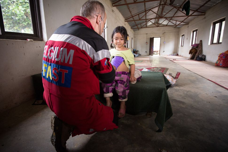 A member of the Belgian B-Fast disaster aid team takes care of a local child in Gorkha, Nepal, on Thursday April 30, 2015.