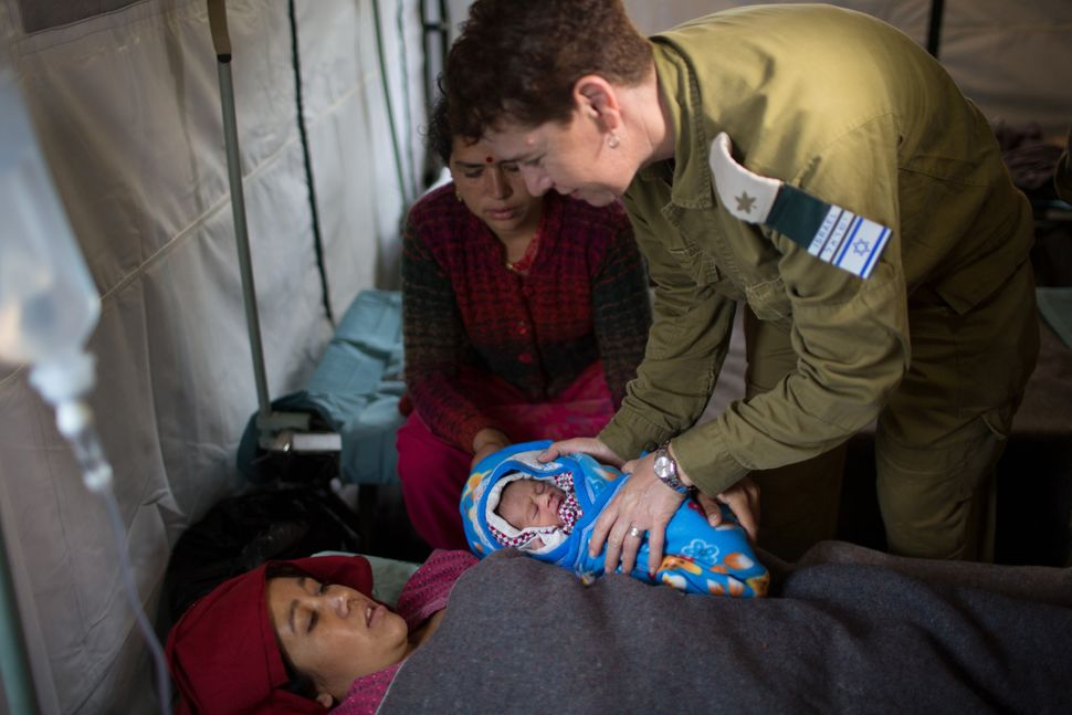 Nepalese woman Quqila Pondari looks at her baby who was born during the night April 30, 2015, at the Israeli field hospital i