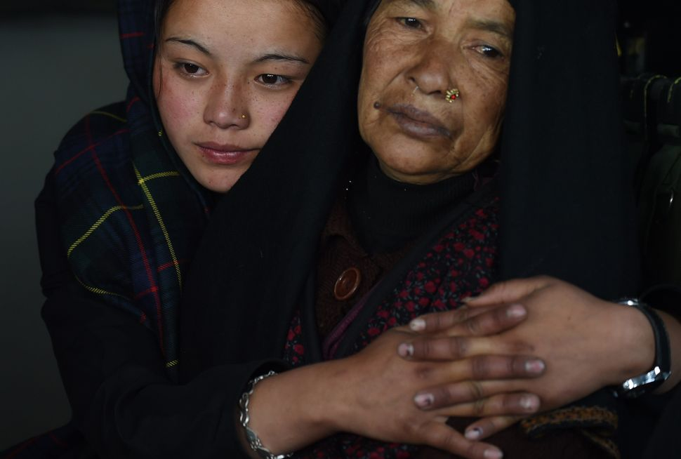 A Nepalese injured mother and daughter sit inside an Indian Army helicopter after they were rescued from Laprak village, in n