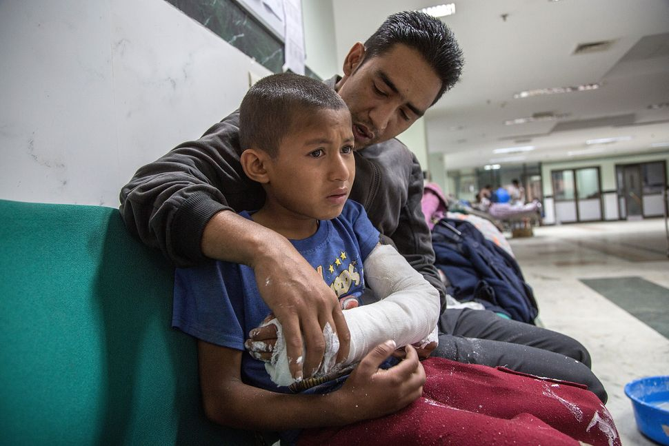 An injured boy is comforted by his father at the National Trauma Center in Kathmandu on April 29, 2015.