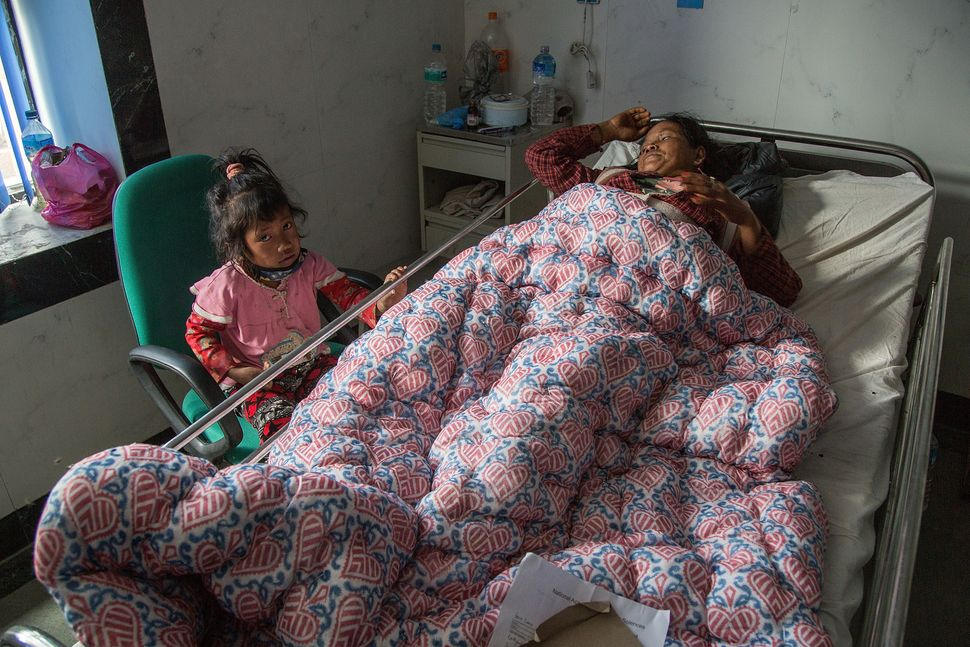 An injured survivor lies in bed while her young daughter sits nearby inside the National Trauma Center on April 29, 2015 in K