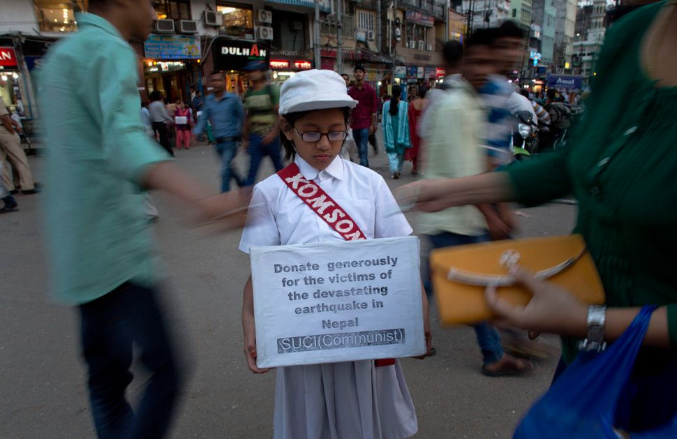 An Indian schoolgirl holds a donation box to raise funds for earthquake victims in Gauhati, India, on Thursday, April 30, 201