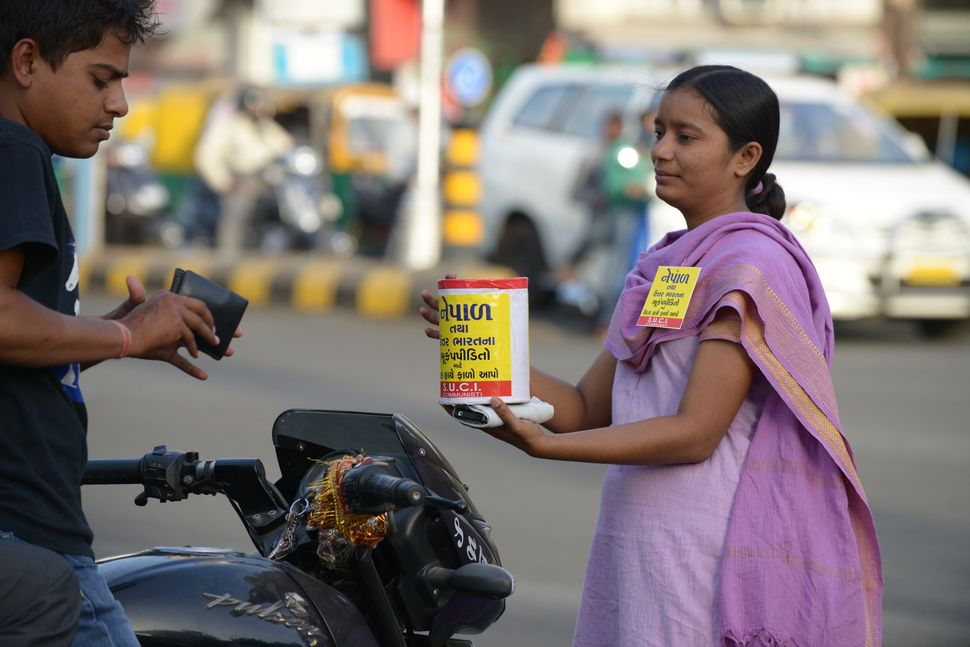 An Indian volunteer from the Socialist Unity Centre of India collects funds from citizens in Ahmedabad for earthquake victims