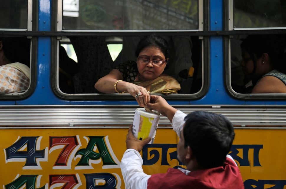 A commuter donates to an earthquake relief fund in Kolkata, India, on Wednesday, April 29, 2015.
