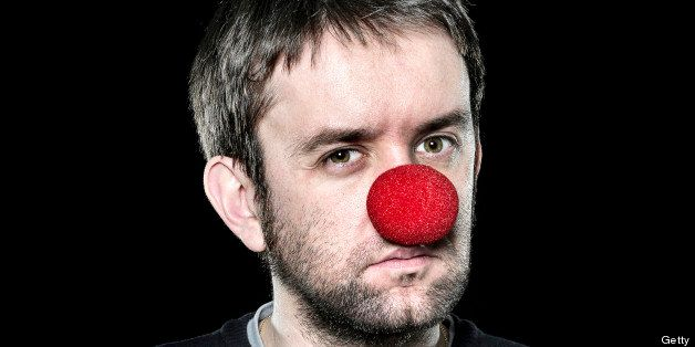 Serious man with red nose on black background