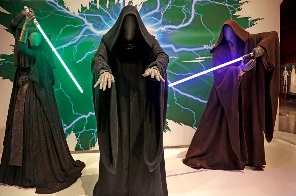 In this photo taken Thursday, Jan. 29, 2015, Sith robes and lightsabers are displayed as part of an exhibit on the costumes o