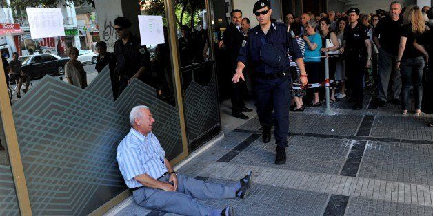 An elderly man is crying outside a national bank branch as pensioners queue to get their pensions, with a limit of 120 euros,