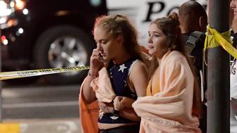 "People walk away from the scene Thursday, Nov. 8, 2018, in Thousand Oaks, Calif. where a gunman opened fire Wednesday inside a country dance bar crowded with hundreds of people on ""college night,"" wounding 11 people including a deputy who rushed to the scene. Ventura County sheriff's spokesman says gunman is dead inside the bar. (AP Photo/Mark J. Terrill)"