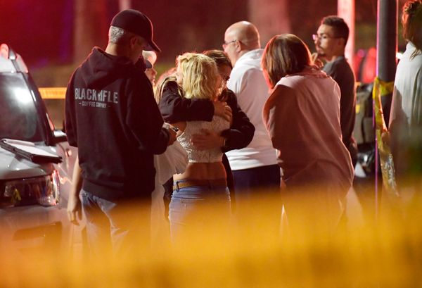 People comfort each other as they stand near the scene.