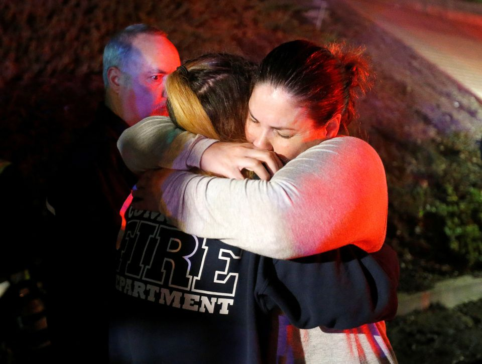 People comfort each other after a mass shooting at a bar in Thousand Oaks, California.
