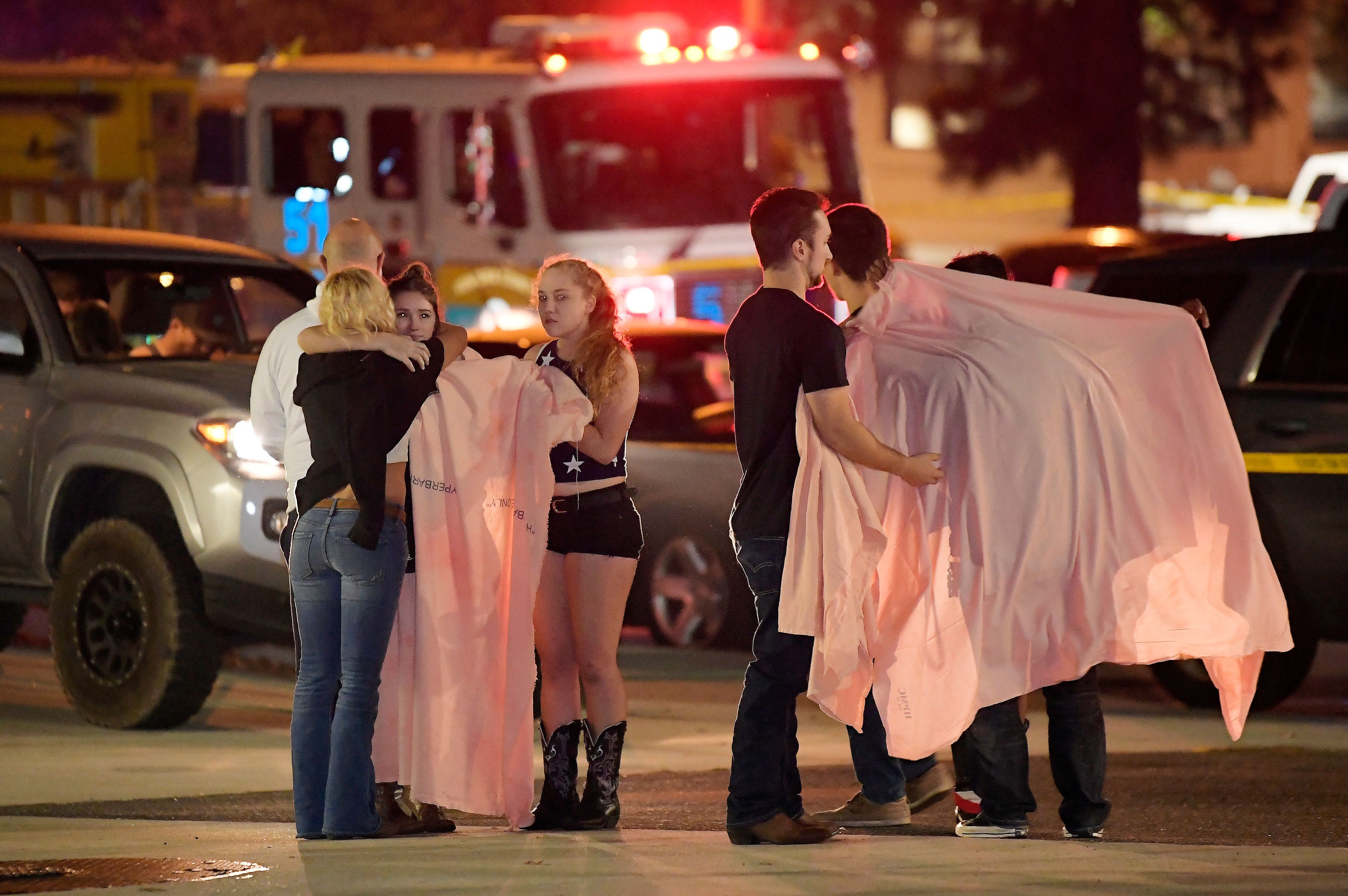 """People comfort each other as they stand near the scene Thursday, Nov. 8, 2018, in Thousand Oaks, Calif. where a gunman opened fire Wednesday inside a country dance bar crowded with hundreds of people on """"college night,"""" wounding 11 people including a deputy who rushed to the scene. Ventura County sheriff's spokesman says gunman is dead inside the bar. (AP Photo/Mark J. Terrill)"""