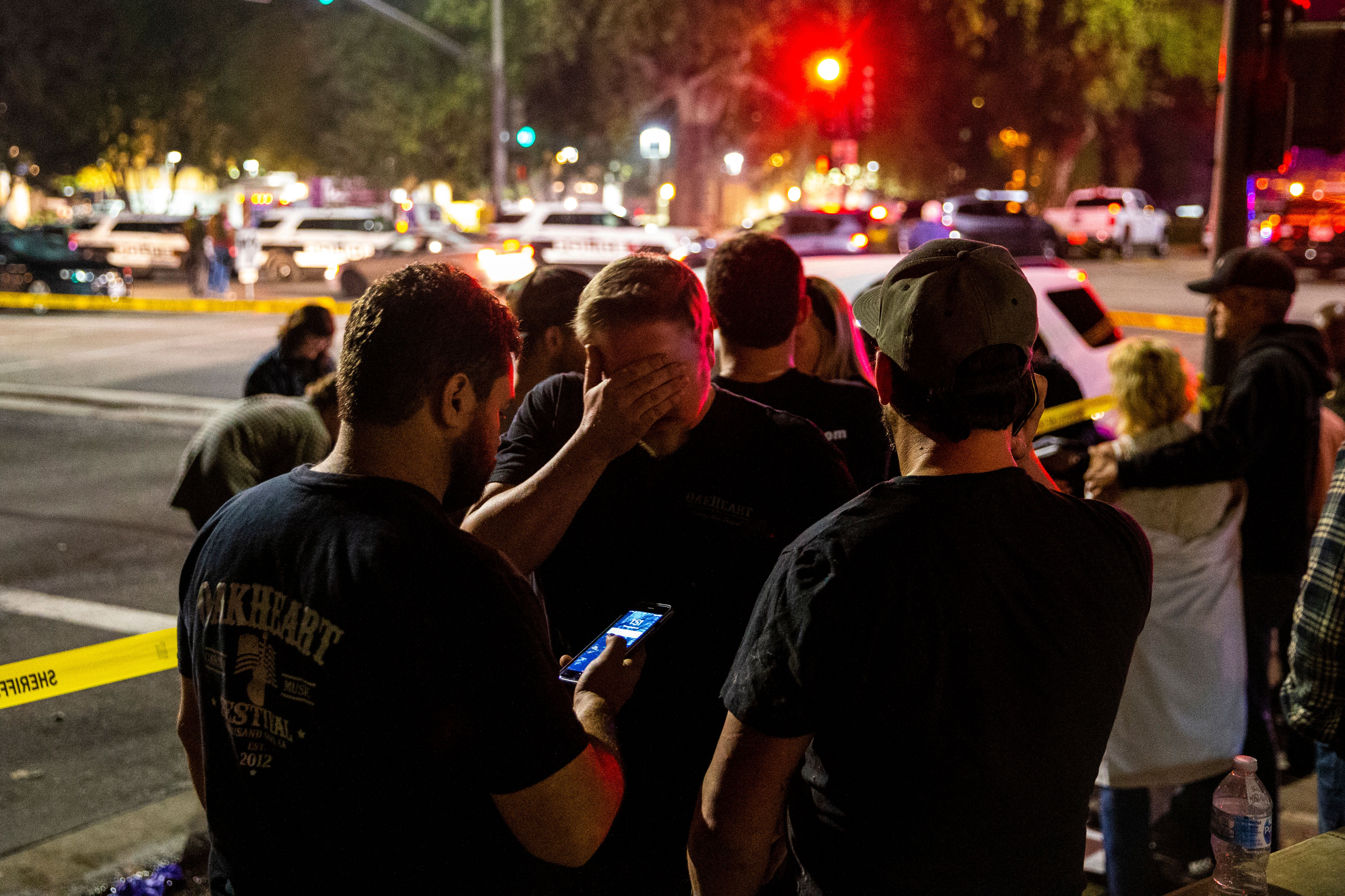 THOUSAND OAKS, CA - NOVEMBER 08: People stand in a parking lot along South Moorpark Road in the aftermath of a mass shooting at Borderline Bar & Grill after a gunman opened fire late Wednesday at a Thousand Oaks bar packed with hundreds of people attending a popular event for college students, causing multiple fatalities on November 8, 2018 in Thousand Oaks, California. The gunman burst into the bar around 11:20 p.m., cloaked in all black as he threw smoke bombs and began shooting at targets as young as 18 inside the Borderline Bar & Grill, authorities and witnesses said. (Photo by Kent Nishimura / Los Angeles Times via Getty Images)