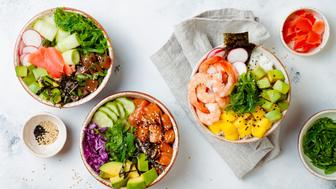 Hawaiian salmon, tuna and shrimp poke bowls with seaweed, avocado, mango, pickled ginger, sesame seeds. Top view, overhead, flat lay