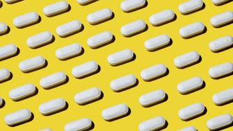 A bottle full of neatly ordered graphic pills on a bright yellow background