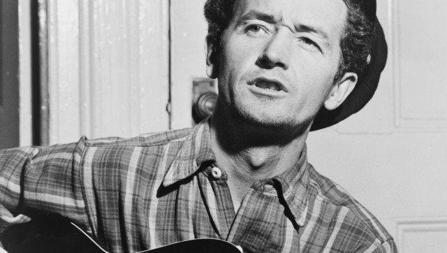 Description Woody Guthrie, half-length portrait, facing slightly left, holding guitar / World Telegram photo by Al Aumuller.