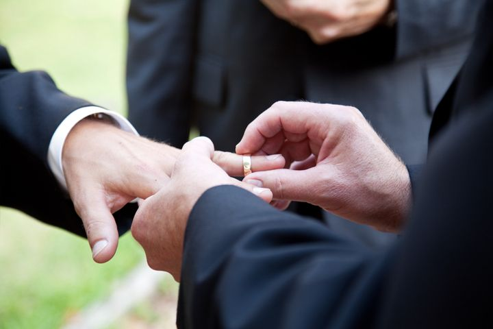 one groom placing the ring on...