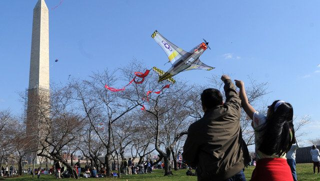 People fly kites near the Washington Monument on March 30, 2013 during the annual Blossom Kite Festival in Washington, DC. Th