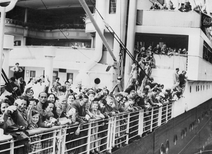 A crowd of Jewish refugees aboard the MS St. Louis ocean liner wave as they arrive in Antwerp, Belgium, after being denied re