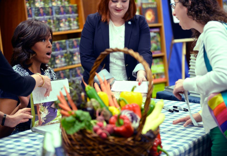 US First Lady Michelle Obama (L) signs a copy of her book 'American Grown: The Story of the White House Kitchen Garden and Ga