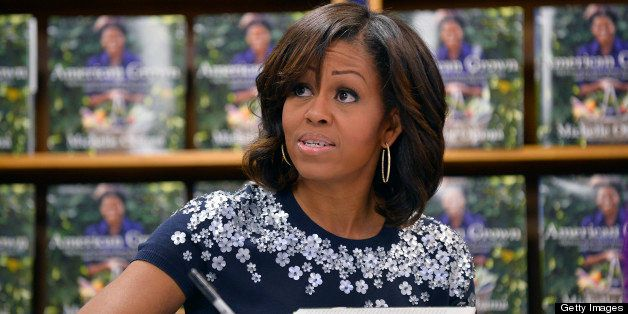 US First Lady Michelle Obama signs a copy of her book 'American Grown: The Story of the White House Kitchen Garden and Garden