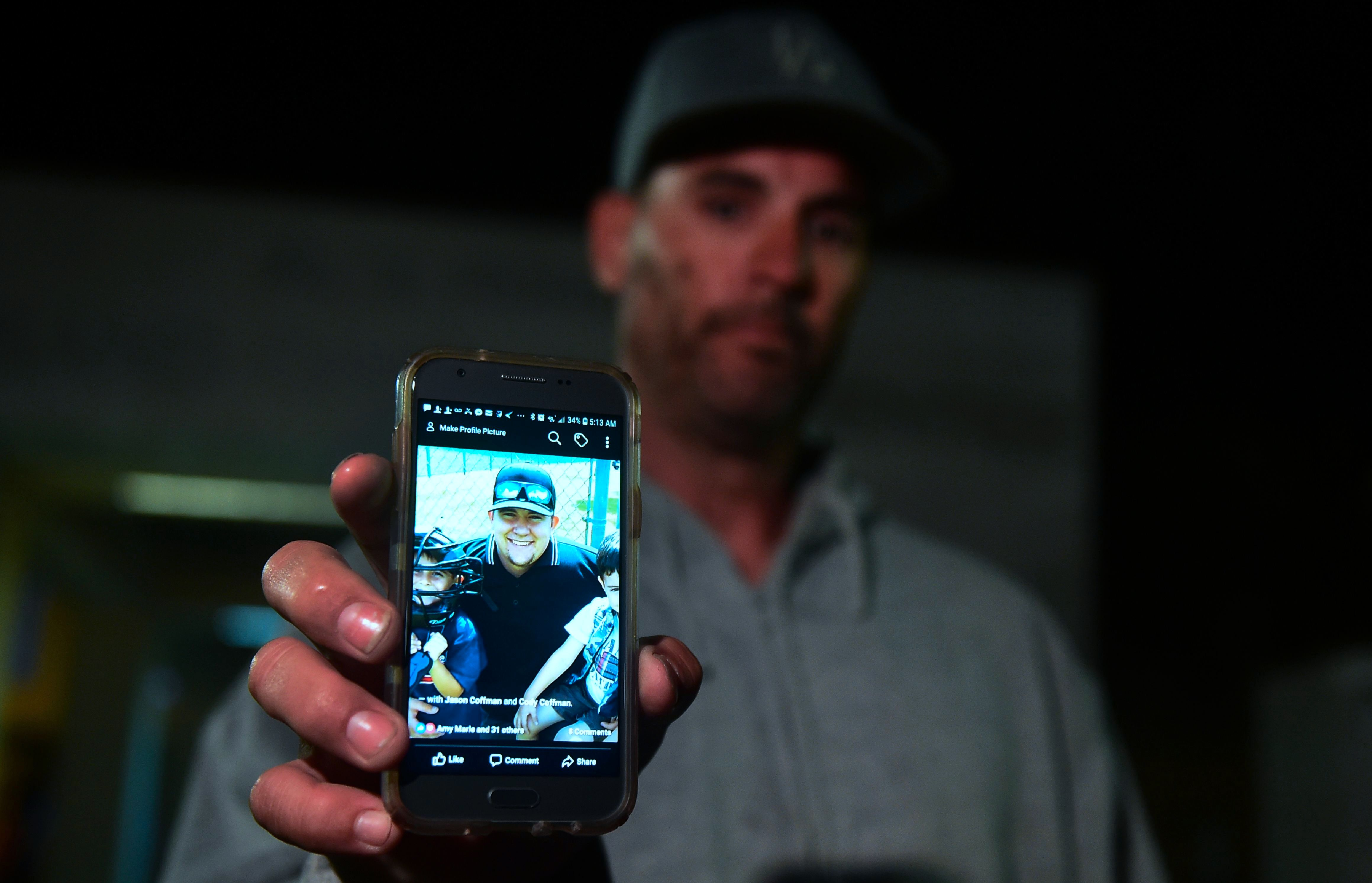 Jason Coffman displays a photo of his son Cody, who was shot and killed at the Borderline Bar & Grill on Nov. 7, 2018.