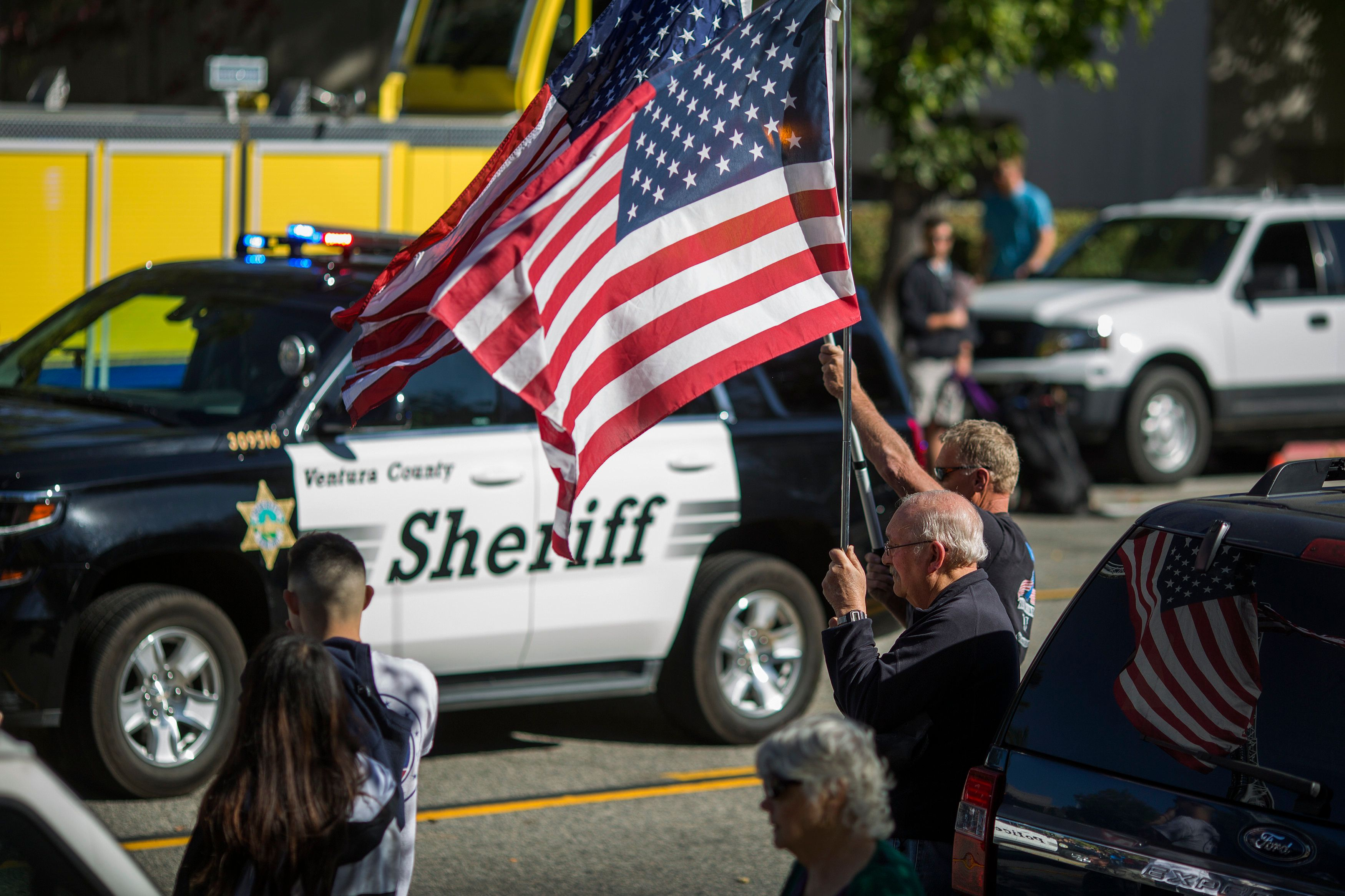 THOUSAND OAKS, CA - NOVEMBER 08: People hold flags as the procession carrying the body of Ventura County Sheriffs Sgt. Ron Helus, who was killed in a mass shooting at the Borderline Bar and Grill, leaves Los Robles Hospital on November 8, 2018 in Thousand Oaks, California. Twelve people were killed, including the sergeant and the gunman, after a mass shooting at the Borderline Bar and Grill in Thousand Oaks late Wednesday night.  (Photo by David McNew/Getty Images)