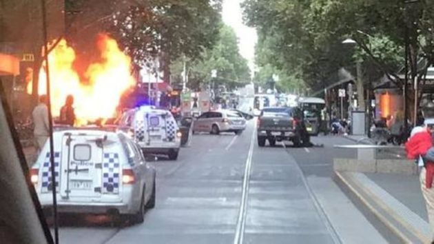 A car was seen ablaze in a central Melbourne street on Friday after a man stabbed several