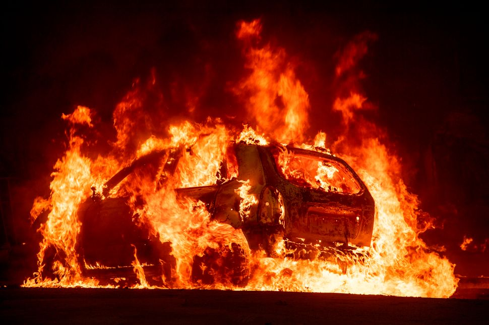 A car explodes into flames as the Camp fire tears through downtown Paradise, California on Nov. 8.