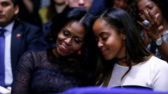 U.S. first lady Michelle Obama and her daughter Malia embrace as President Barack Obama praises them during his farewell address in Chicago, Illinois, U.S. January 10, 2017. REUTERS/Jonathan Ernst
