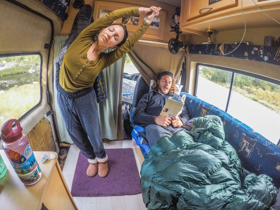Brittany and Drew relaxing inside their van the day after summiting the highest peak in Norway, August 2017.