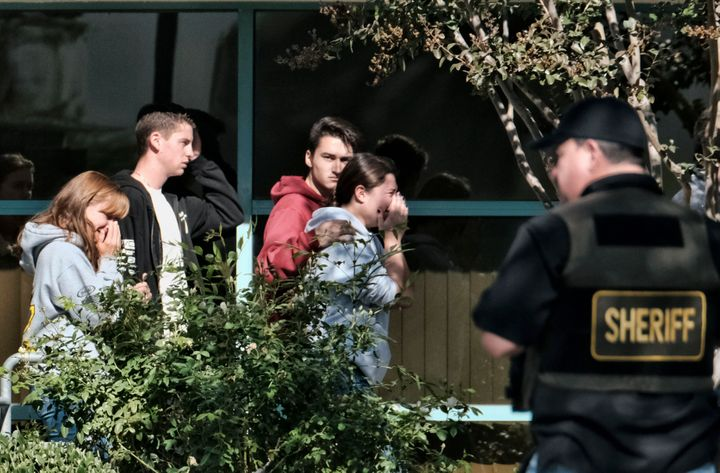 Grieving people are led into the Thousand Oaks Teen Center where families have gathered after a deadly shooting at a bar on N
