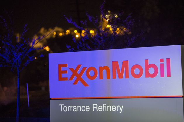 Flames from flaring glow behind the Exxon Mobil logo at a refinery in