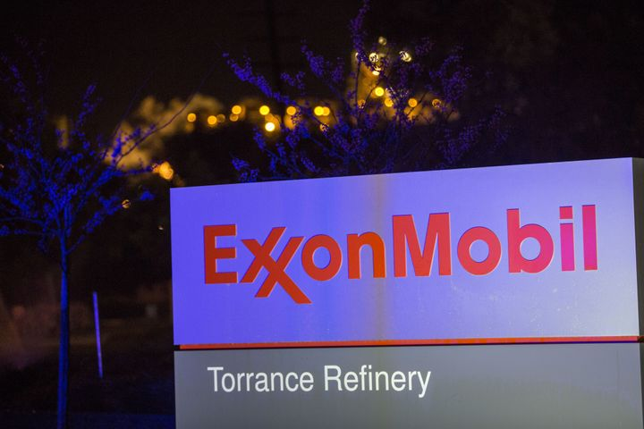 Flames from flaring glow behind the Exxon Mobil logo at a refinery in California.