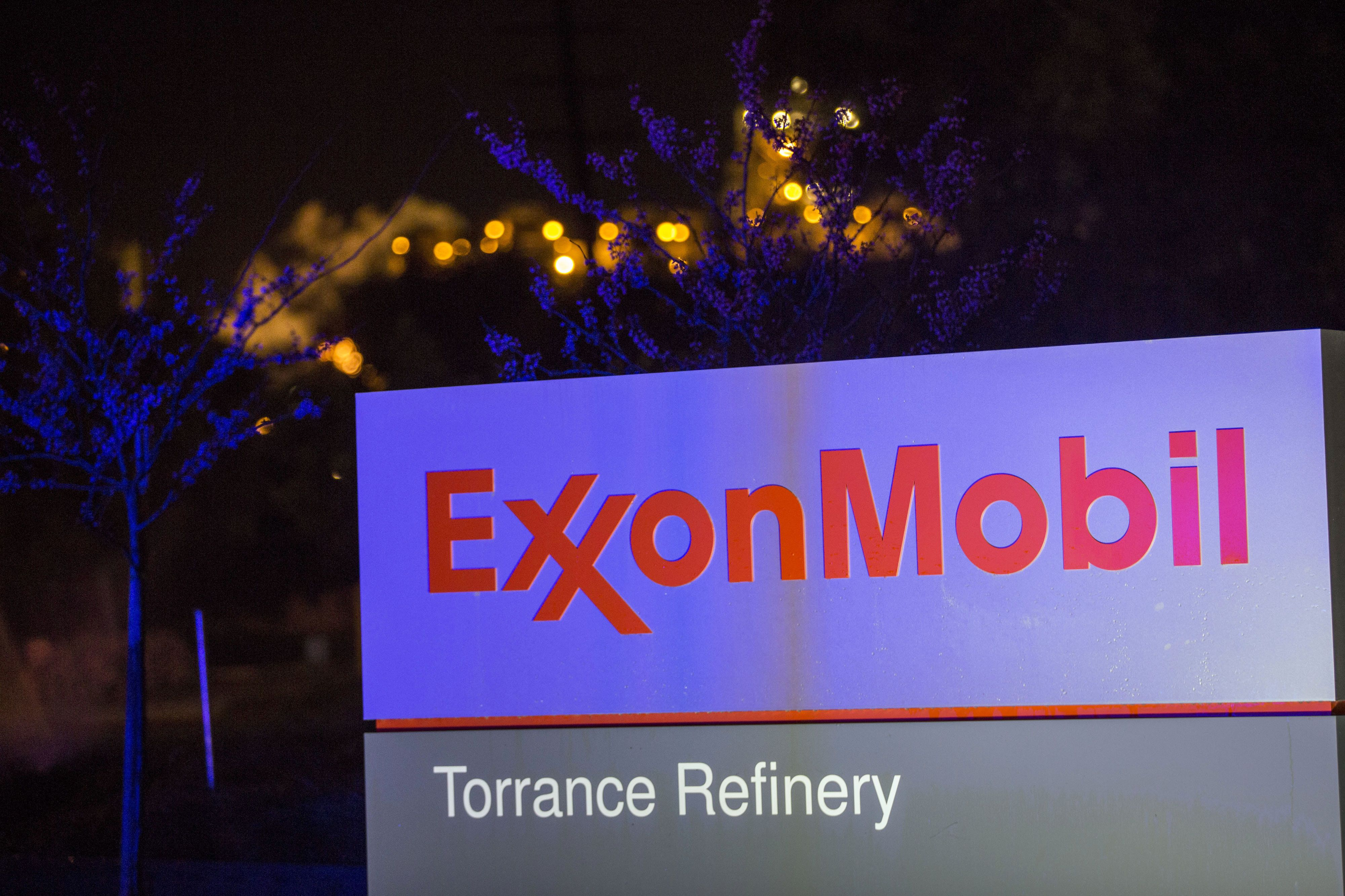 Lights from a police car are reflected on Exxon Mobil Corp. signage displayed at the company's Torrance Refinery in Torrance, California, U.S., on Wednesday, March 16, 2016. City officials said a 'flaring event' at the refinery, which led local residents to report smoke and fire in the air on social media, was caused by a power outage. Photographer: Patrick T. Fallon/Bloomberg via Getty Images