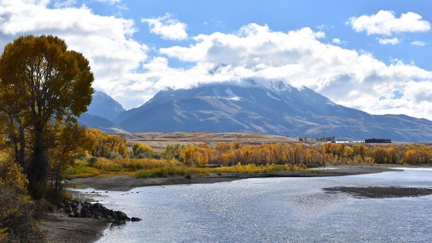 Emigrant Peak is seen rising above the Paradise Valley and the Yellowstone River near Emigrant, Mont., Monday, Oct. 8, 2018. U.S. Interior Sec. Ryan Zinke has announced a 20-year ban on new mining claims on public lands in Montana, north of Yellowstone National Park. (AP Photo/Matthew Brown)