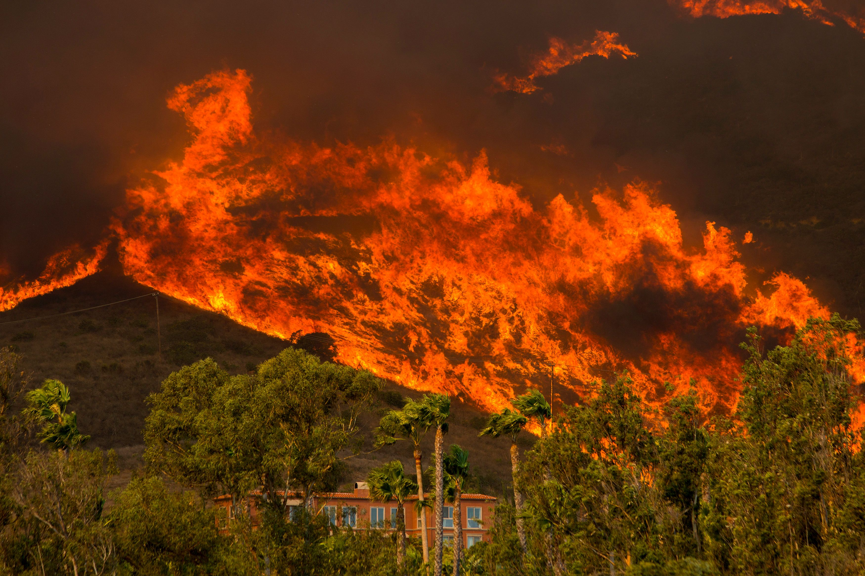 MALIBU, CA - NOVEMBER 09: The Woolsey Fire approaches homes on November 9, 2018 in Malibu, California. About 75,000 homes have been evacuated in Los Angeles and Ventura counties due to two fires in the region.(Photo by David McNew/Getty Images)