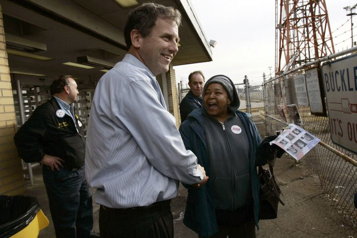 Brown shakes hands with workers as they leave the Ford Engine Plant in 2006 in Brook Park, Ohio.
