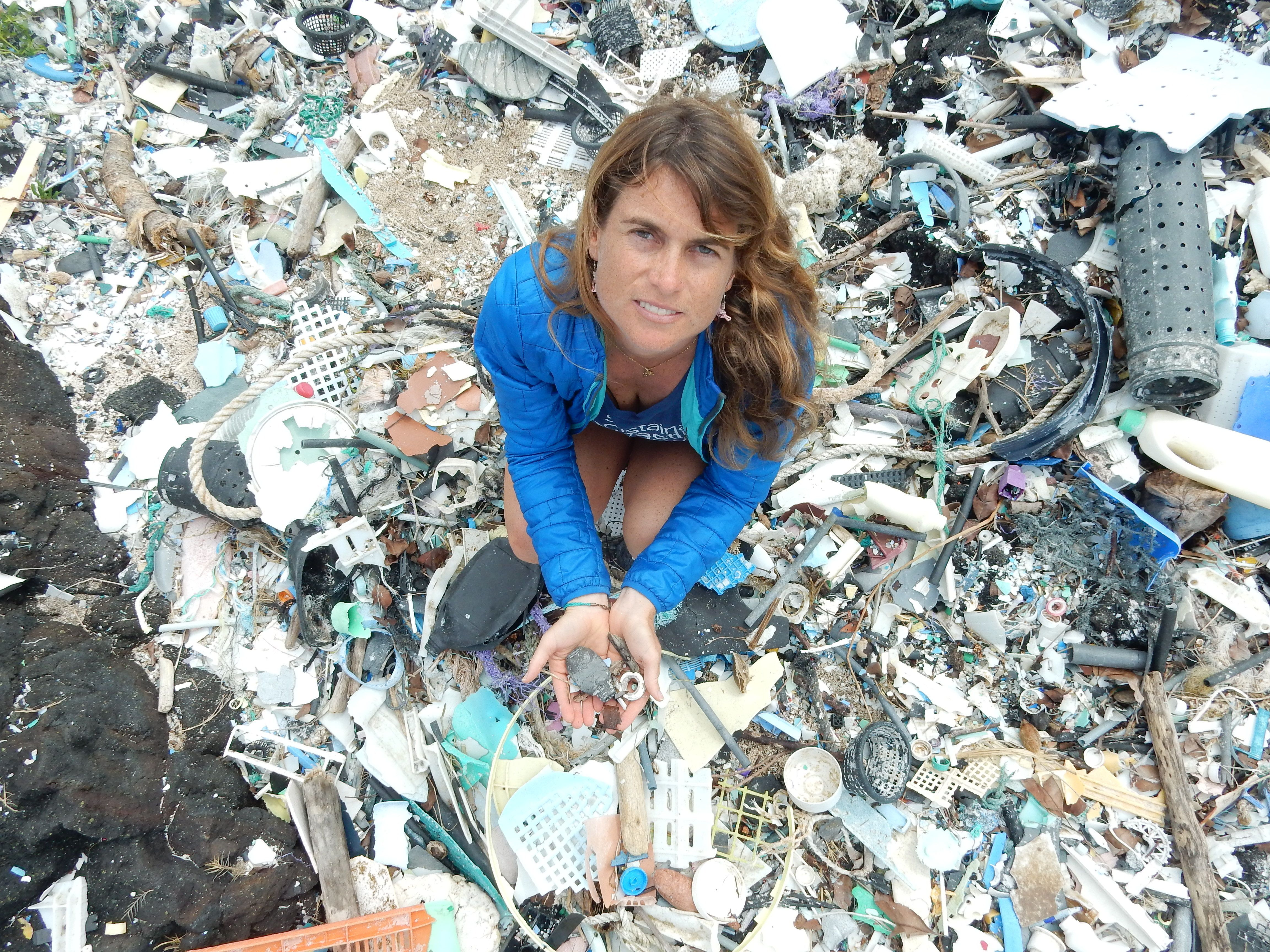 Sarah-Jeanne Royer stands atop a mound of plastic debris. Earlier this year, she found that ocean plastics can decay into gre
