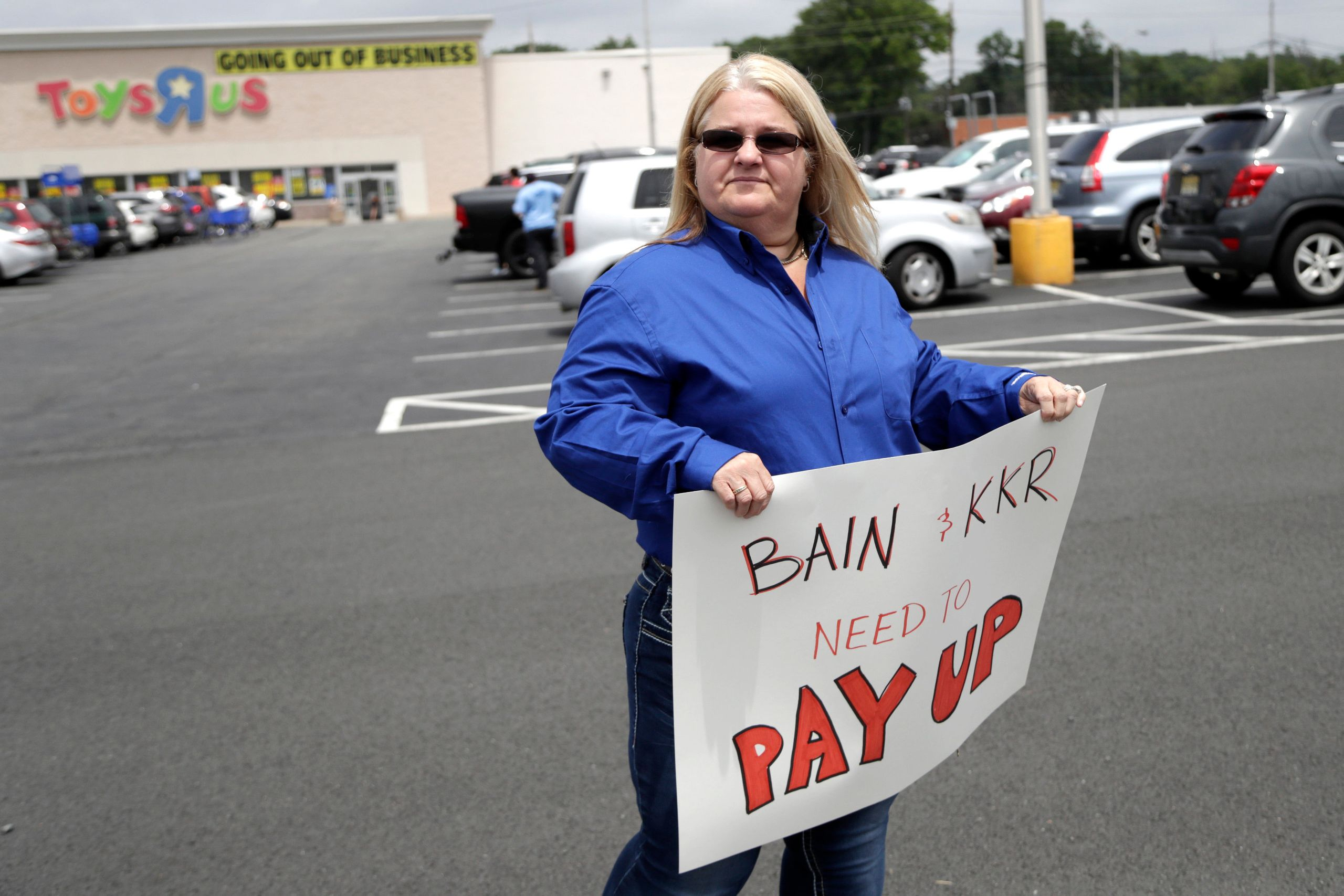 Cheryl Claude, an assistant manager at the Toys R Us store in Woodbridge, New Jersey, holds a sign in front of the Totowa, lo