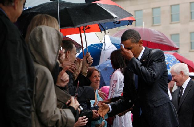 Barack Obama wipes the rain off his face as he meets Pentagon staff and family members of the victims...
