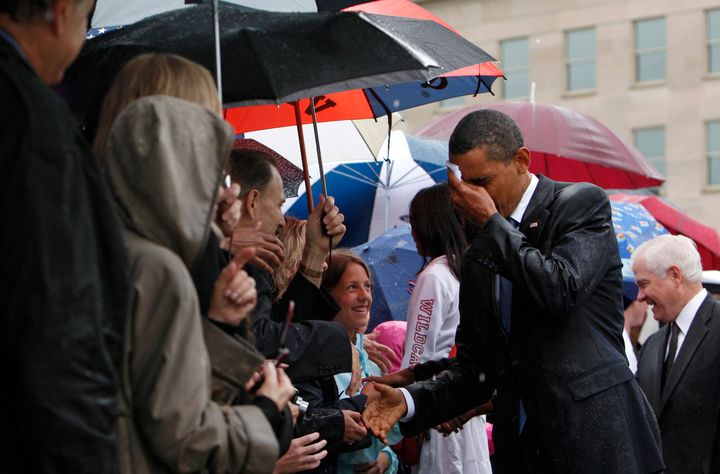 Barack Obama wipes the rain off his face as he meets Pentagon staff and family members of the victims of the September 11 att