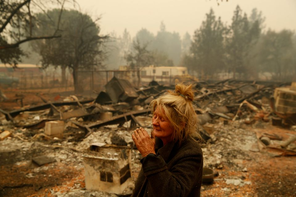 Cathy Fallon stands near the charred remains of her home in Paradise,