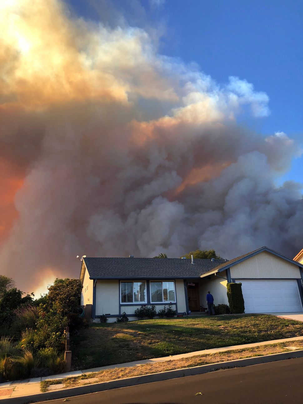 Plumes of smoke loom in the sky several miles away, seen behind a home in Thousand Oaks, Calif.