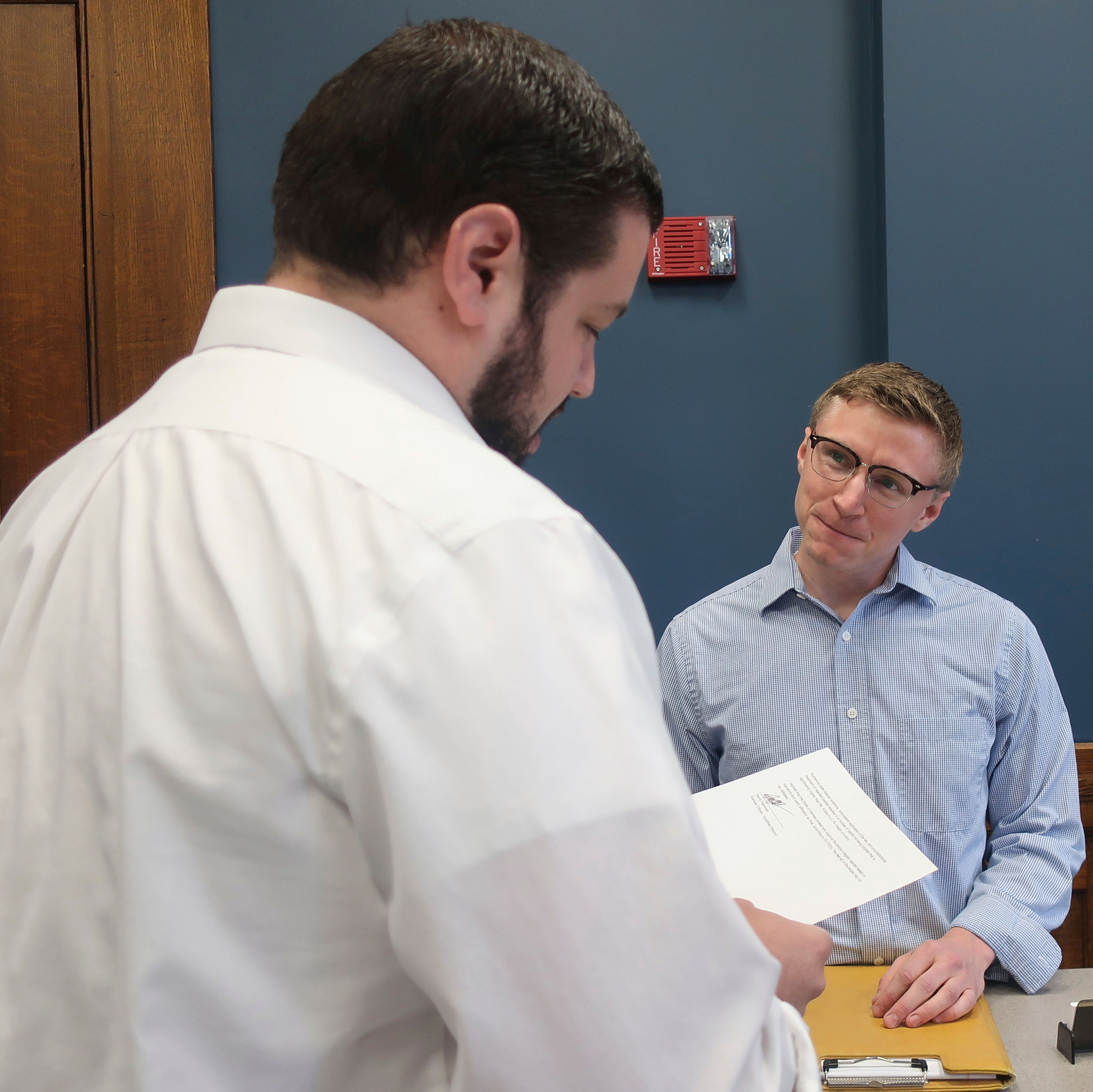 Davis Hammet, right, a Topeka, Kan., resident and liberal activist, presents his challenge to Kansas Secretary of State Kris Kobach appearing on the November ballot as the GOP nominee for governor to assistant state elections director Jameson Beckner, left, Thursday, Sept. 6, 2018, in Topeka, Kan. Hammet alleges that hundreds of legal ballots were not counted in the August primary, which Kobach won by 343 votes. (AP Photo/John Hanna)