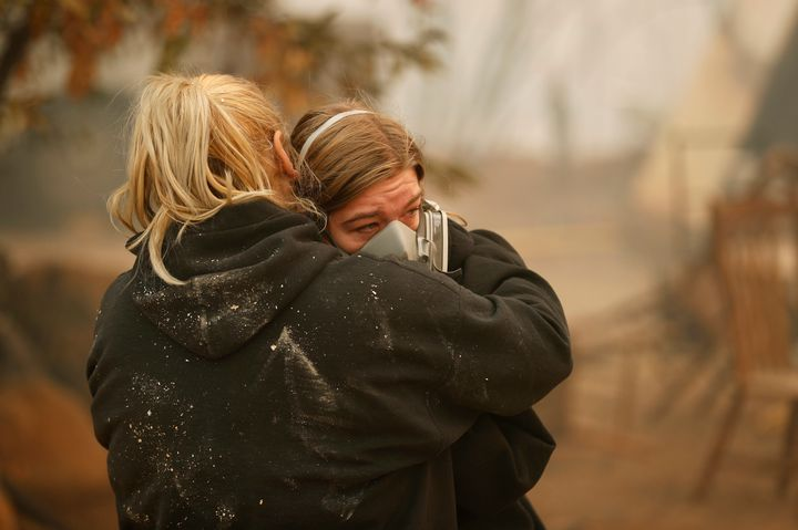 Krystin Harvey, left, comforts her daughter Araya Cipollini at the remains of their home burned in the Camp Fire, Saturday, N