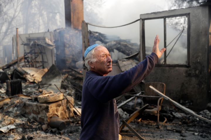 John Honigsfeld surveys the damage to a neighbor's property after a wildfire swept through Saturday, Nov. 10, 2018, in Malibu