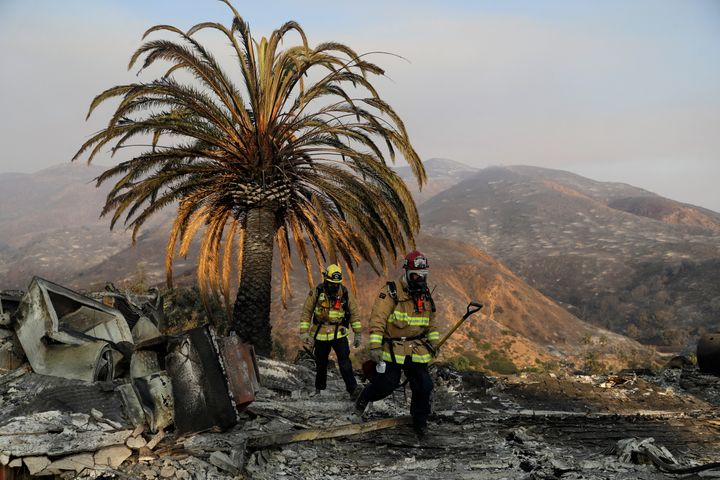 Firefighters Jason Toole, right, and Brent McGill with the Santa Barbara Fire Department walk among the ashes of a wildf